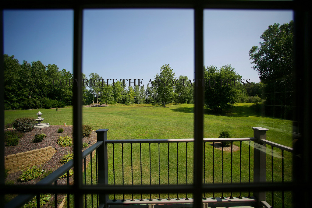 . This is the view of an expansive backyard from inside a luxury home on Wednesday, July 30, 2014, in Springfield, Ill. The home is located near The Rail Golf Course, on the 5 acres of land, next to 66 acres of recreation zoned land and timber. (AP Photo/Seth Perlman)