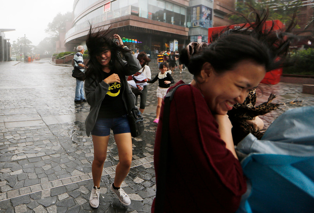 . Tourists brave strong wind at the Victoria Peak in Hong Kong Tuesday, Aug. 13, 2013. The Observatory said Typhoon Utor intensified slightly as it moves towards the western coast of Guangdong. The typhoon battered the northern Philippines on Monday, toppling power lines and dumping heavy rain across cities and food-growing plains. (AP Photo/Kin Cheung)