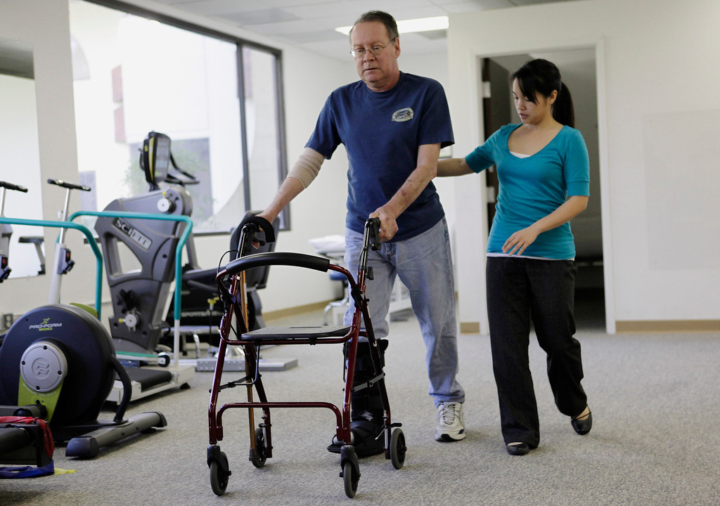 . Gary Richards, Mercury News Roadshow columnist, practices walking with Physical Therapist, Lisa Yee, during a therapy session for a heel problem in Cupertino, Calif. on Thursday, Feb. 28, 2013. Richards  is the Mercury News Roadshow columnist who is calling attention to aging motorists and the issues they face. (Gary Reyes/ Staff)