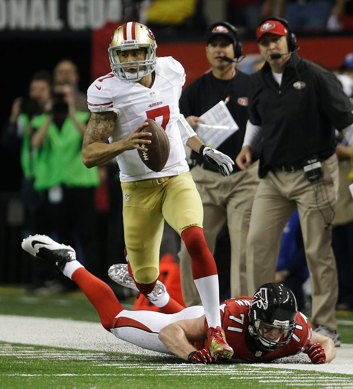 . San Francisco 49ers\' Colin Kaepernick runs past Atlanta Falcons\' Kroy Biermann during the first half of the NFL football NFC Championship game Sunday, Jan. 20, 2013, in Atlanta. (AP Photo/Dave Martin)