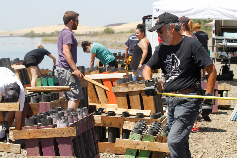 Firework producer with Pyro Spectaculars Richard Bryant (right) arranges the tubes that hold the fireworks July 3, 2017 at the Thermalito Forebay in Oroville, California.  (Emily Bertolino -- Mercury-Register)