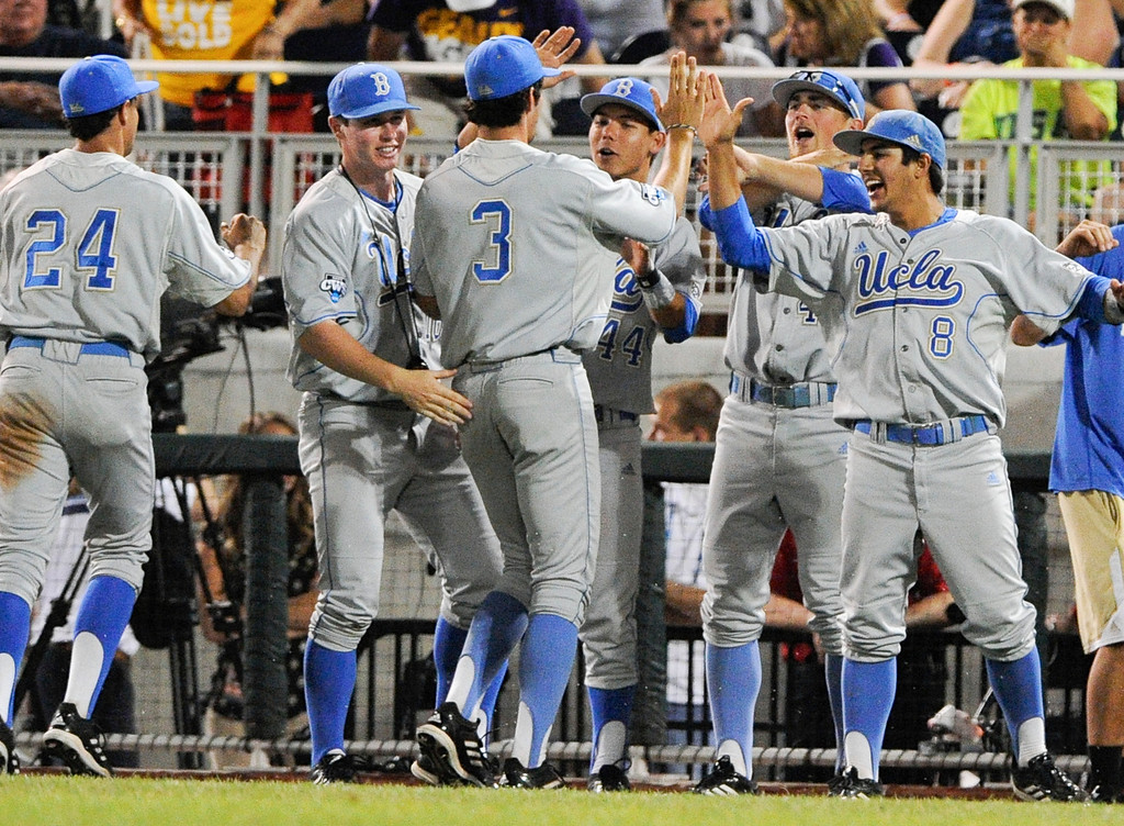 . UCLA players, including Trent Chatterton (8) celebrate with outfielder Christoph Bono (3) after he caught a fly ball hit by North Carolina State\'s Trea Turner to end the eighth inning of an NCAA College World Series game in Omaha, Neb., Tuesday, June 18, 2013. Two North Carolina State runners were left stranded. UCLA won 2-1. (AP Photo/Eric Francis)
