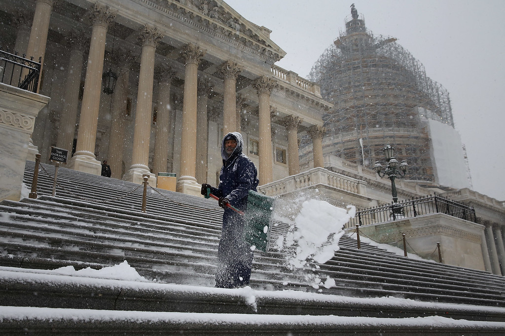 . WASHINGTON, DC - JANUARY 06:  Clearing a path for the new Congress, employees of the Architect of the Capitol shovel snow off the steps of the U.S. House of Representatives as more snow continues to fall January 6, 2015 in Washington, DC. Tuesday is the opening day of the 114th Congress. (Photo by Chip Somodevilla/Getty Images)