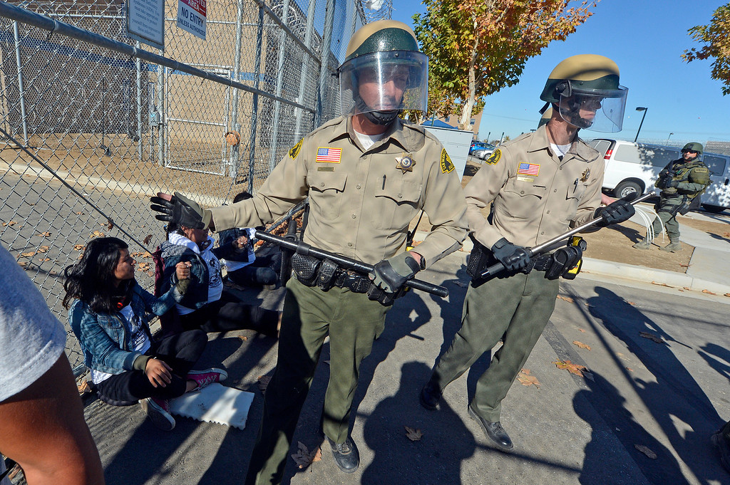 . San Bernardino County Sheriff deputies push protesters off the grounds of the Adelanto Detention Facility East as 3 three of the protesters remain after locking themselves to the prisons gates Monday. Over 100 protesters took part in a peaceful rally Monday November 25, 2013 at the privately owned Adelanto Detention Facility in Adelanto, Calif. The protesters, with the Inland Empire Immigrant Coalition, were protesting  to demand the release of three prisoners on ICE holds who they say shouldn\'t be incarcerated because they\'re infractions were minor and they\'ve been in too long already. It comes in the wake of highly critical report recently released by the nonprofit Detention Watch Network, detailing alleged abuses and civil rights violations of prisoners at the Adelanto facility and nine similar institutions nationwide.(Will Lester/Inland Valley Daily Bulletin)