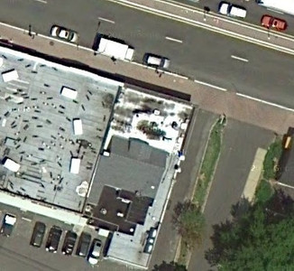 This satellite photo shows the house in the previous photo with a commercial building built around it. We don't know if they did it to save money or perhaps the guy just wouldn't leave.
