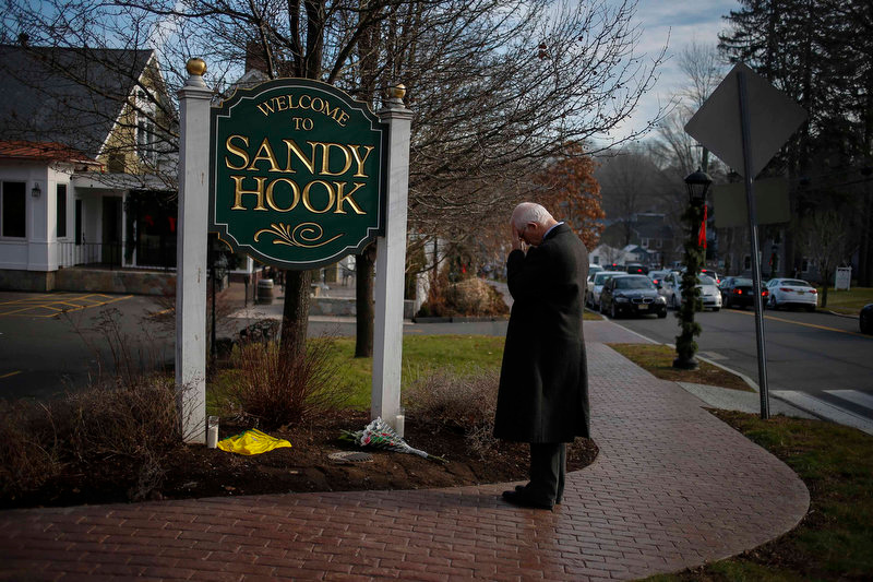 Description of . New Jersey resident Steve Wruble, who was moved to drive out to Connecticut to support local residents, grieves for victims of an elementary school mass shooting at the entrance to Sandy Hook village in Newtown, Connecticut December 15, 2012. Investigators have found