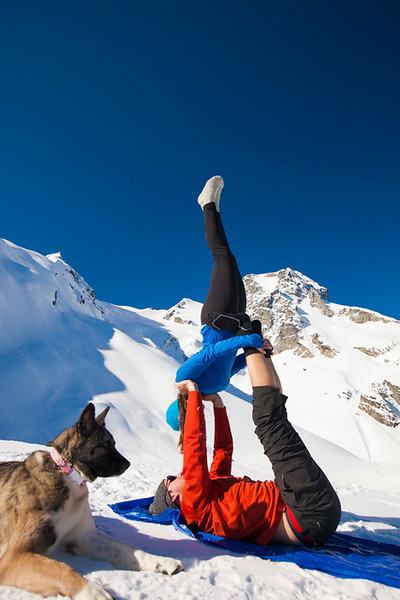 A fit couple preform Acro Yoga outside in the snow beside their dog.
