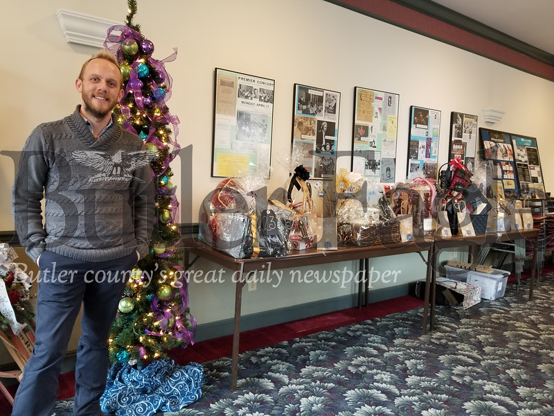 Jared Sullivan, the Butler Downtown president, poses with some of the silent auction baskets available at the Butler County Symphony Association office on Small Business Saturday, which will be held on Saturday from 10 a.m. to 2 p.m.