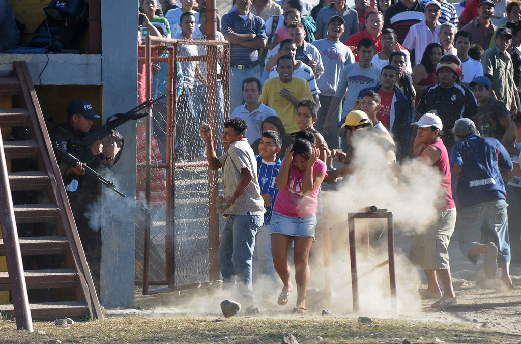 . In this Feb. 15, 2012 file photo, inmates relatives clash with police outside a prison after a deadly fire in Comayagua, Honduras.  Over 300 inmates perished in the fire that swept through the prison north of Tegucigalpa. More than half the inmates were still awaiting trial.  Many of those who died had been locked up for petty crimes: stealing a wallet, robbing a truck. Some had never been charged. (AP Photo/Fernando Antonio, File)