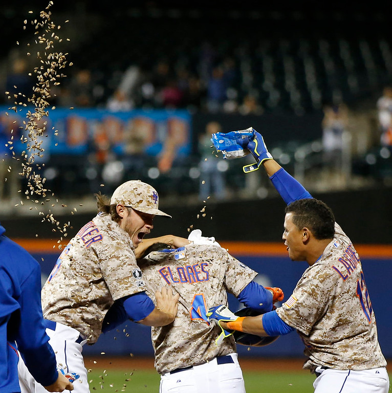 . New York Mets Matt den Dekker, left, celebrates with the Mets Wilmer Flores as Juan Lagares (12) dumps sunflower seeds on Flores\'s head after Flores hit a ninth-inning, game-winning, walk-off, sacrifice fly, allowing Curtis Granderson to score the go-ahead run in the Mets 3-2 victory over the Colorado Rockies in a baseball game in New York, Monday, Sept. 8, 2014. (AP Photo/Kathy Willens)