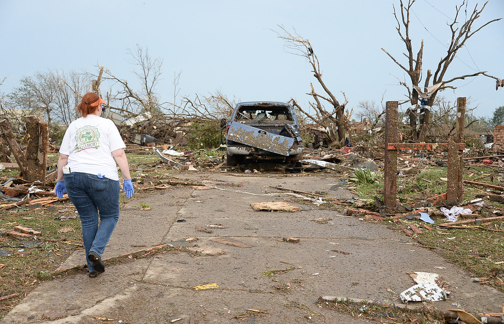 . A woman looks at a truck that is the only thing left at a house that was destroyed.