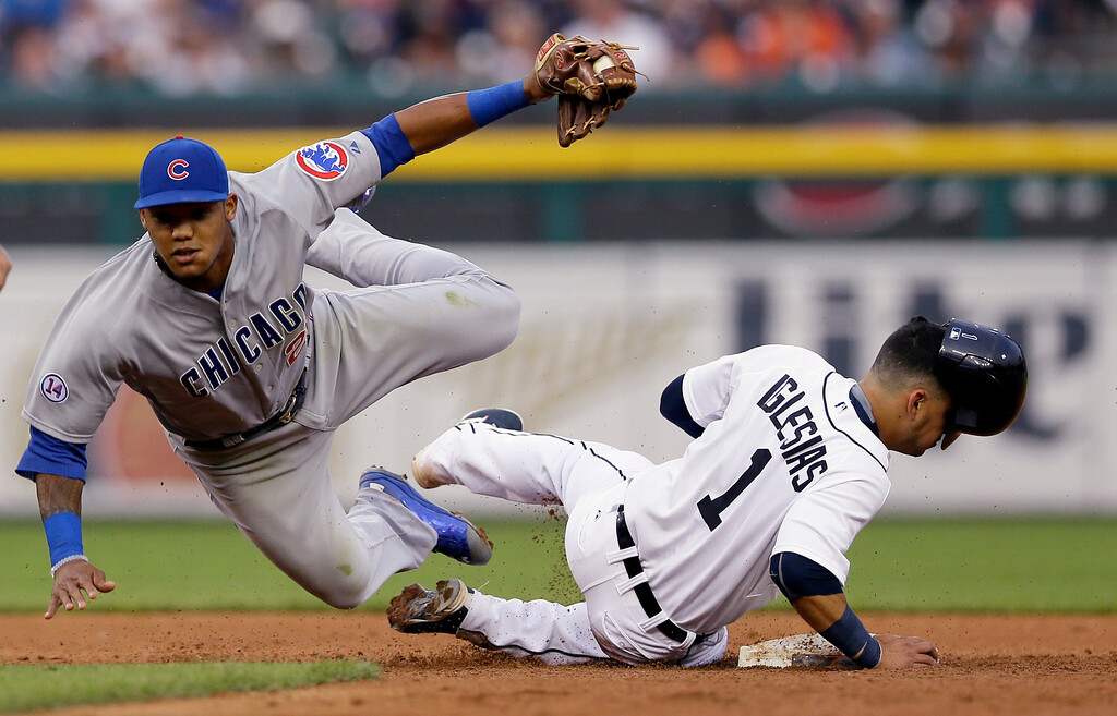 . Chicago Cubs second baseman Addison Russell tumbles next to Detroit Tigers\' Jose Iglesias after tagging Iglesias out on an attempted steal during the fifth inning of a baseball game, Tuesday, June 9, 2015, in Detroit. (AP Photo/Carlos Osorio)