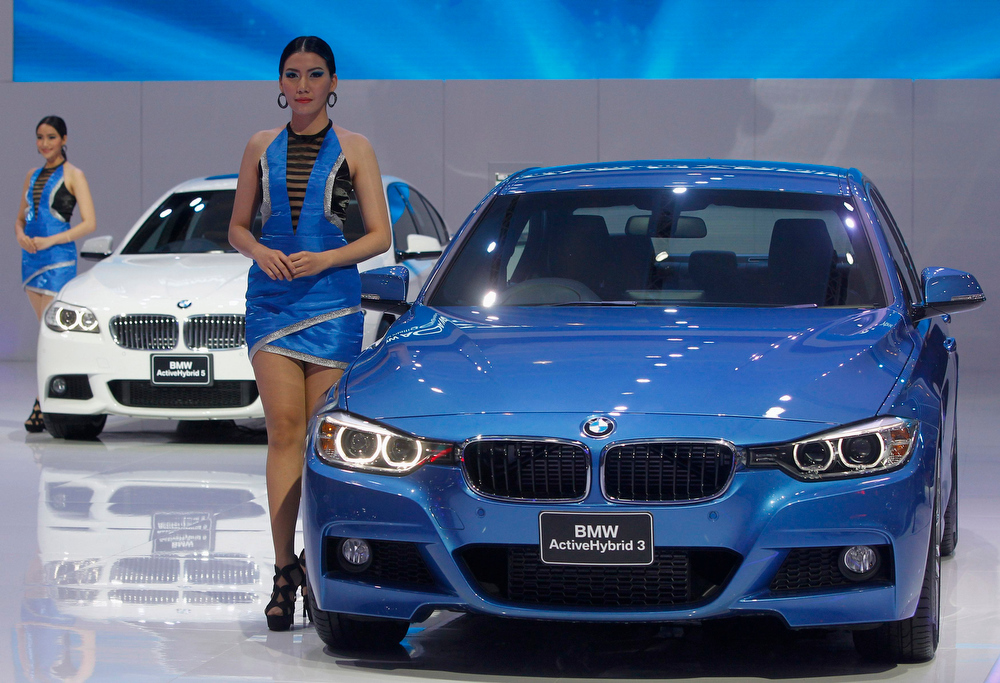 . A model poses beside a BMW Active Hybrid 3 during a media presentation of the 34th Bangkok International Motor Show in Bangkok March 26, 2013. The Bangkok International Motor Show will be held from March 27 to April 7. REUTERS/Chaiwat Subprasom