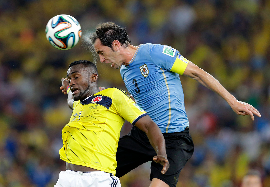 . Uruguay\'s Diego Godin and Colombia\'s Jackson Martinez go for a header during the World Cup round of 16 soccer match between Colombia and Uruguay at the Maracana Stadium in Rio de Janeiro, Brazil, Saturday, June 28, 2014. (AP Photo/Antonio Calanni)