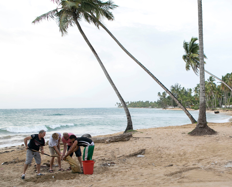 . People make their own sandbags to protect in their homes before the arrival of Hurricane Irma in Las Terrenas, Dominican Republic, Wednesday, Sept. 6, 2017. Dominicans are getting ready for the arrival of Hurricane Irma after battering Puerto Rico with heavy rain and powerful winds, leaving more than 600,000 people without power as authorities struggle to get aid to small Caribbean islands already devastated by the historic storm.(AP Photo/Tatiana Fernandez)