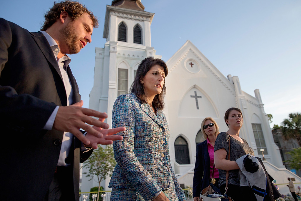 . Escorted by staff and security, South Carolina Governor Nikki Haley (C) moves from one television interview to another across from the historic Emanuel African Methodist Episcopal Church June 19, 2015 in Charleston, South Carolina. Haley called for the death penalty for Dylann Storm Roof, 21, of Lexington, South Carolina, if he is found guilty of murdering nine people during a prayer meeting at the church Wednesday night. Among the dead is the Rev. Clementa Pinckney, the pastor of the church which, according to the National Park Service, is the oldest black congregation in America south of Baltimore.  (Photo by Chip Somodevilla/Getty Images)