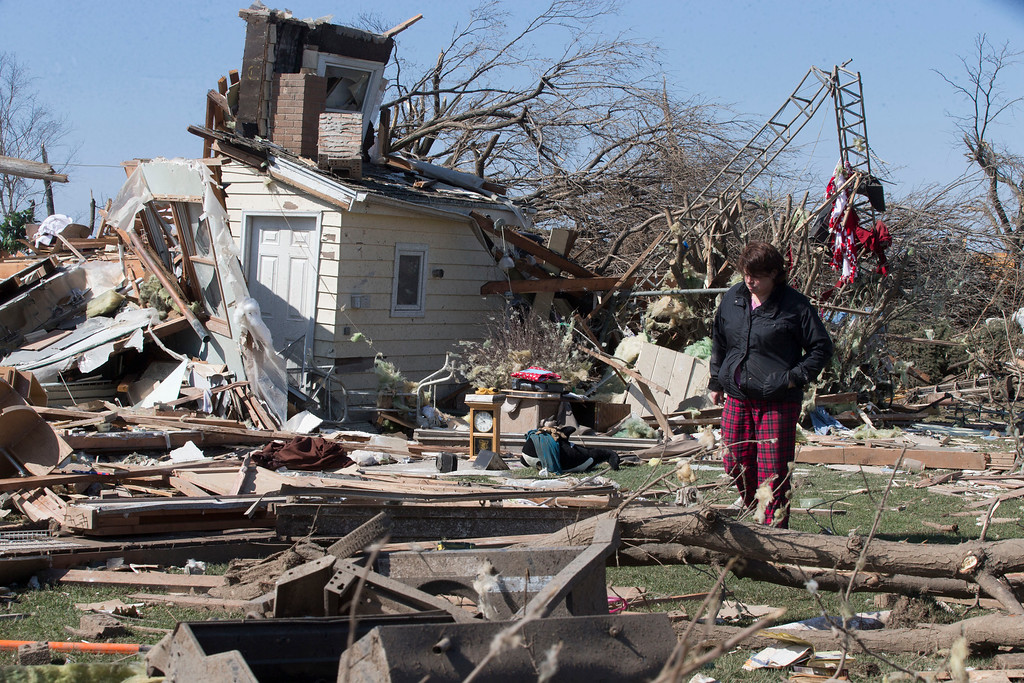 . Ann Schabacker sifts through her scattered belongings Friday morning, April 10, 2015, after her home was destroyed the night  before in Rochelle, Ill. At least two tornadoes swept through Illinois late Thursday.  (AP Photo/Rockford Register Star, Sunny Strader)