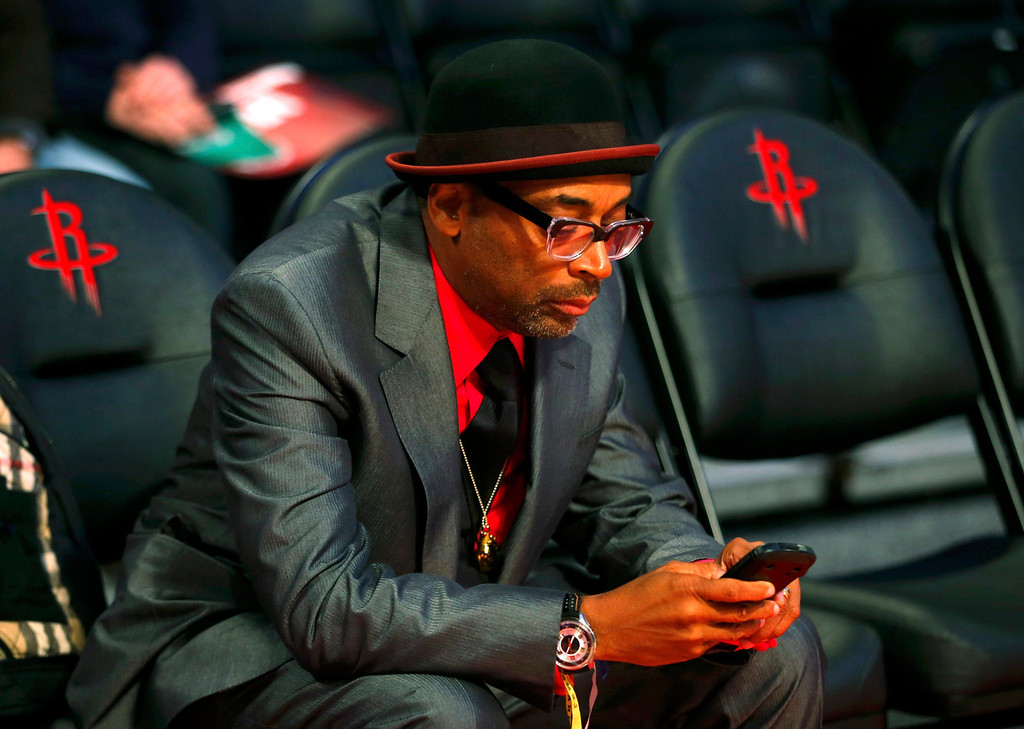 . Film director Spike Lee looks at his phone before the All Star slam dunk competition during the NBA basketball All-Star weekend in Houston, Texas, February 16, 2013. REUTERS/Jeff Haynes