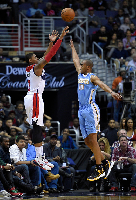 . Washington Wizards guard Bradley Beal (3) takes a shot against Denver Nuggets guard Arron Afflalo (10) during the first half of an NBA basketball game, Friday, Dec. 5, 2014, in Washington. (AP Photo/Nick Wass)