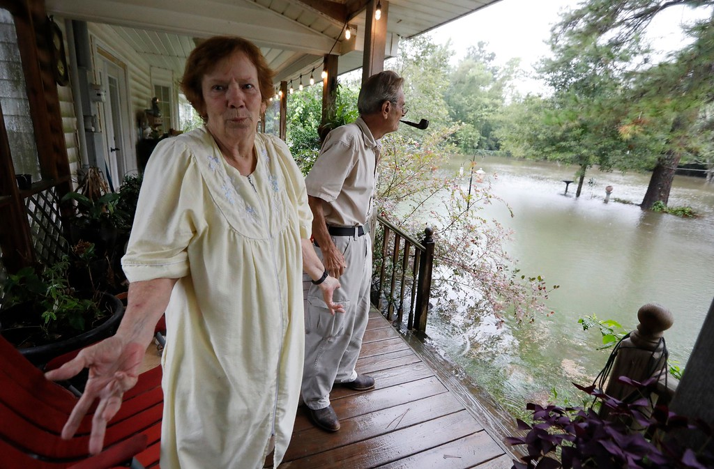 . Brenda Bradley speaks about the flooding in her neighborhood in Moss Bluff, a Lake Charles, La., suburb in Calcasieu Parish, Monday, Aug. 28, 2017. Bradley, 72, and her husband, Jimmie, right, had stacked sandbags at their doors, but the rising water was lapping at the steps to their back porch and had overtaken their front yard. Virtually every neighbor on Crawford Drive has at least a foot of water in their yards. (AP Photo/Rogelio V. Solis)
