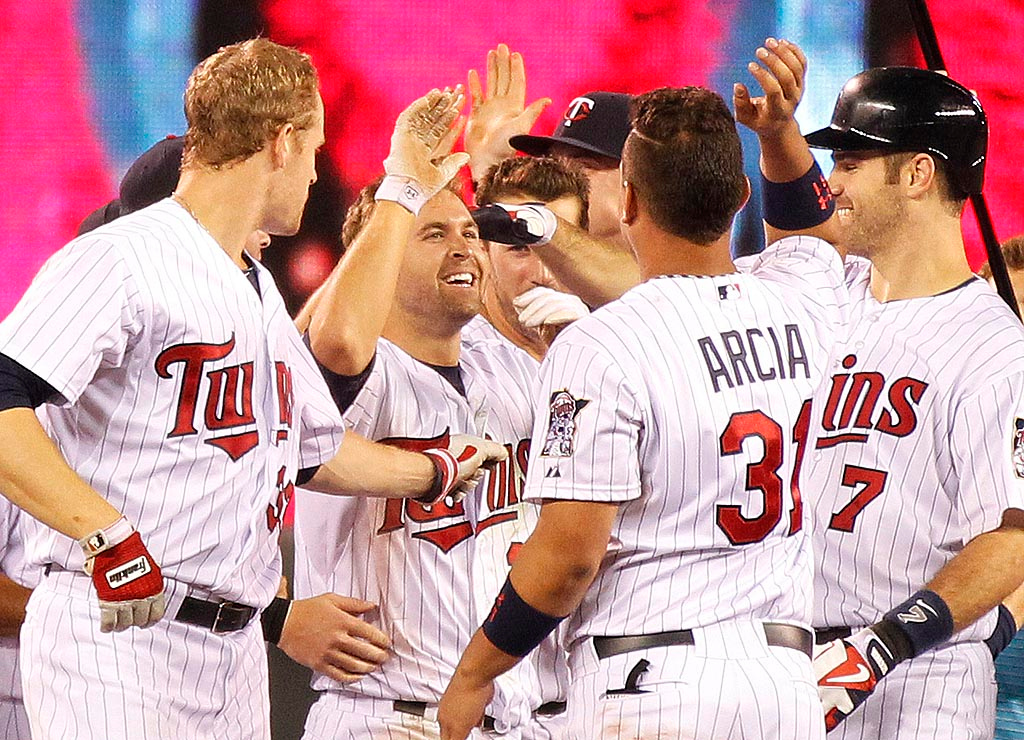 . Brian Dozier is congratulated by teammates after he hit an RBI single scoring Clete Thomas with the winning run in the 13th inning. (AP Photo/Andy Clayton-King)