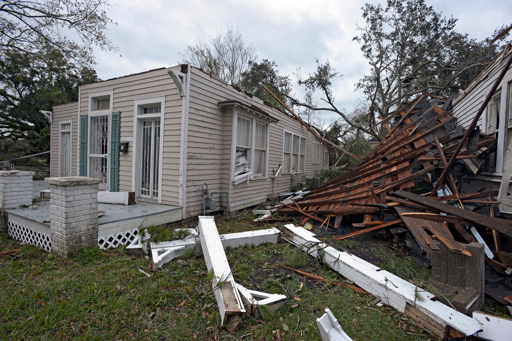 Description of . The roof of a damaged home rests against the side of a neighboring house as residents clean up and assess the damage from a Christmas Day tornado Wednesday, Dec. 26, 2012  in Mobile, Ala. With only a handful of injuries and no deaths reported statewide from the storms, the head of the state's emergency response said it was difficult to fathom how the toll wasn't worse. (AP Photo/G.M. Andrews)