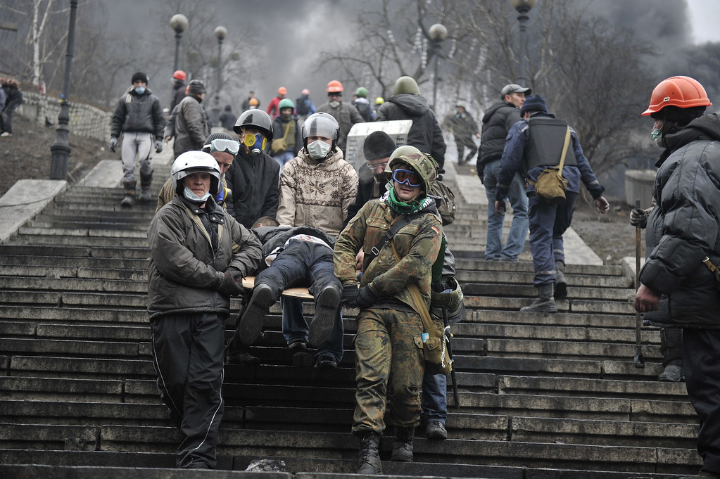 . Protesters carry a wounded demonstrator in Kiev on February 20, 2014. Hundreds of armed protesters charged police barricades Thursday on Kiev\'s central Independence Square, despite a truce called just hours earlier by the country\'s embattled president.  AFP PHOTO / LOUISA GOULIAMAKI/AFP/Getty Images