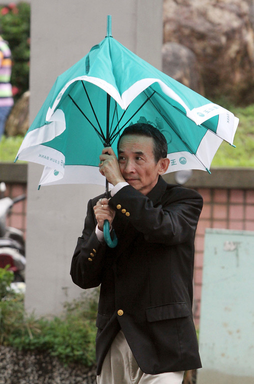. A Taiwanese man holds his umbrella against powerful gusts of wind as Typhoon Fitow approaches in Taipei, Taiwan, Sunday, Oct. 6, 2013. (AP Photo/Chiang Ying-ying)
