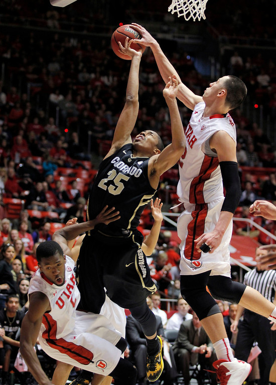 . Colorado guard Spencer Dinwiddie (25) is fouled as he goes to the basket against Utah center Jason Washburn, right, and Utah guard Jarred DuBois, left, in the second half during an NCAA college basketball game Saturday, Feb. 2, 2013 in Salt Lake City. Utah beat Colorado 58-55. (AP Photo/Steve C. Wilson)