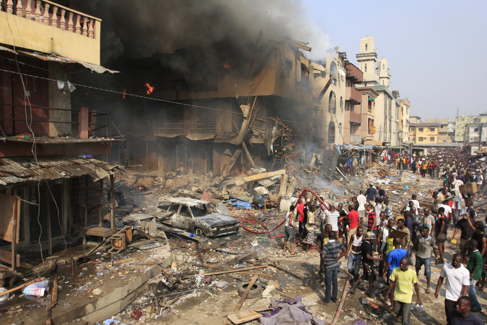 Description of . People gather at the site of a fire on Lagos Island in Lagos, Nigeria, on Wednesday, Dec. 26, 2012. An explosion ripped through a warehouse Wednesday where witnesses say fireworks were  stored in Nigeria's largest city, sparking a fire. It wasn't immediately clear if anyone was injured in the blast that firefighters and locals struggled to contain. (AP Photo/Jon Gambrell)