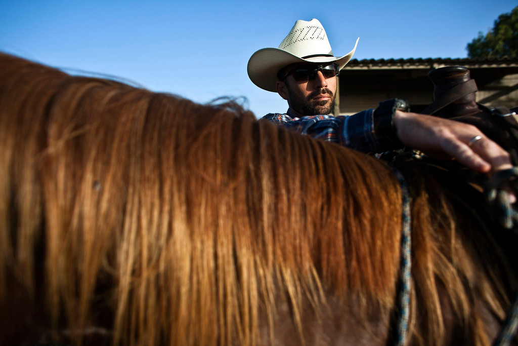 . Alon, an Israeli cowboy, unloads his horse after working with cattle in the early morning, on a ranch just outside Moshav Yonatan, a collective farming community, about 2 km (1 mile) south of the ceasefire line between Israel and Syria in the Golan Heights May 21, 2013.REUTERS/Nir Elias