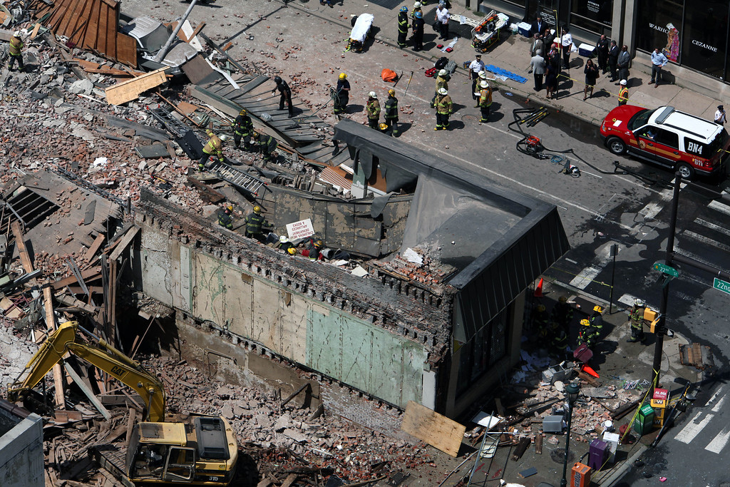 . Rescue personnel search the scene of a building collapse in downtown Philadelphia Wednesday June 5, 2013. (AP Photo/Jacqueline Larma)