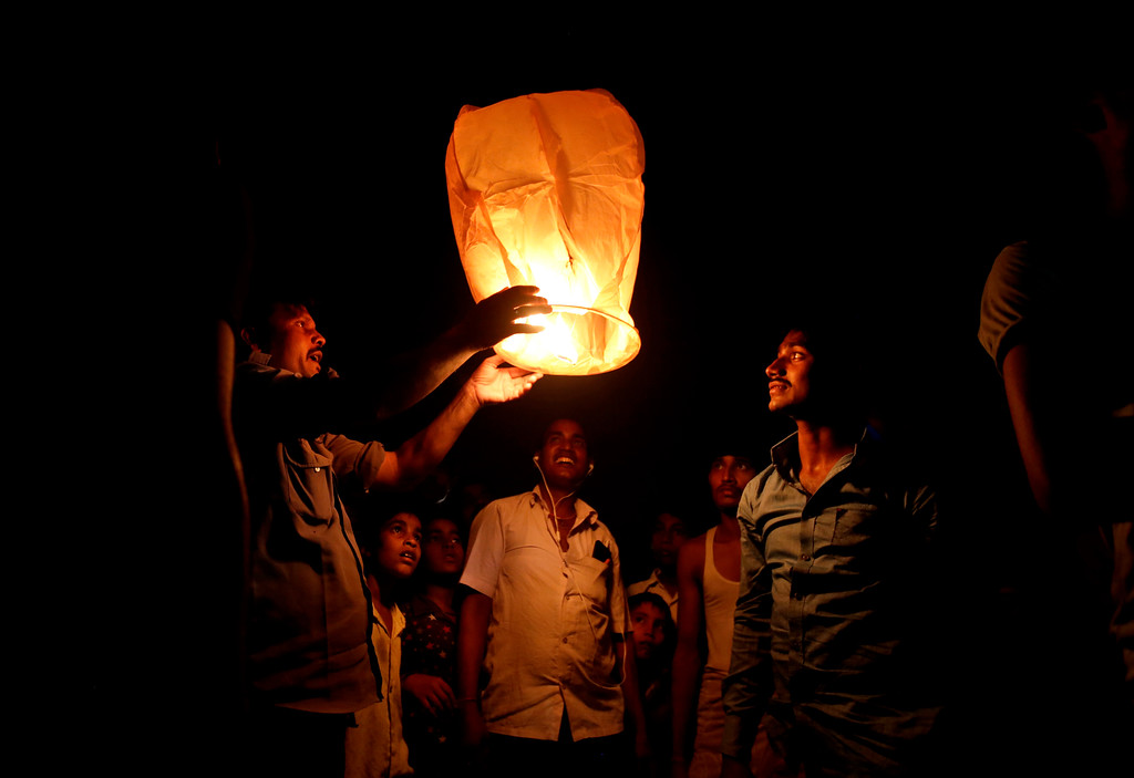 . Indians light a sky lantern to celebrate Diwali festival in New Delhi, India, Thursday, Oct. 19, 2017. Diwali, a major Hindu festival for more than a billion Indians, includes lighting oil lamps or candles to symbolize a victory of knowledge over ignorance, light over darkness and good over evil. (AP Photo/Altaf Qadri)