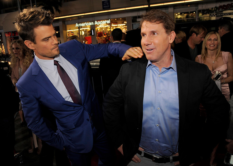 """. Josh Duhamel, left, a cast member in \""""Safe Haven,\"""" dusts off the jacket of producer Nicholas Sparks, author of the book upon which the film is based, at the U.S. premiere of the film, Tuesday, Feb. 5, 2013, in the Hollywood section of Los Angeles. (Photo by Chris Pizzello/Invision/AP)"""