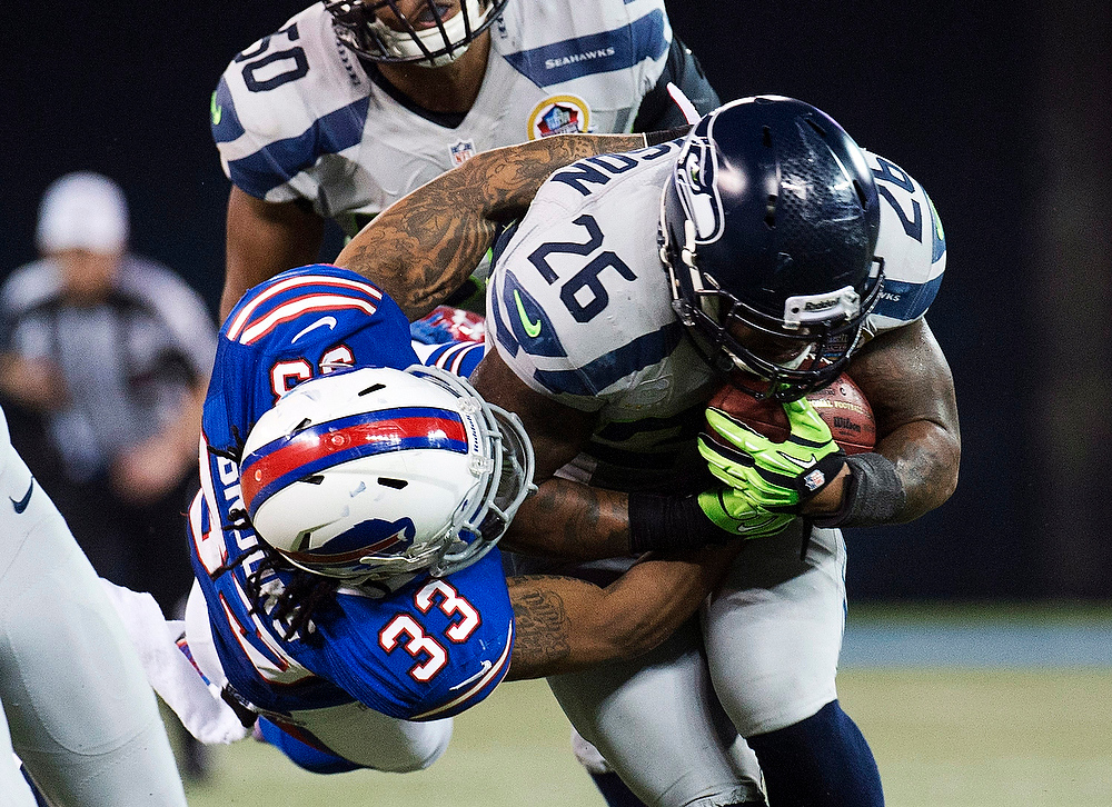 . Buffalo Bills defensive back Ron Brooks (33) tackles Seattle Seahawks fullback Michael Robinson (26) during the second half of an NFL football game, Sunday, Dec. 16, 2012, in Toronto. The Seahawks won 50-17. (AP Photo/The Canadian Press, Nathan Denette)