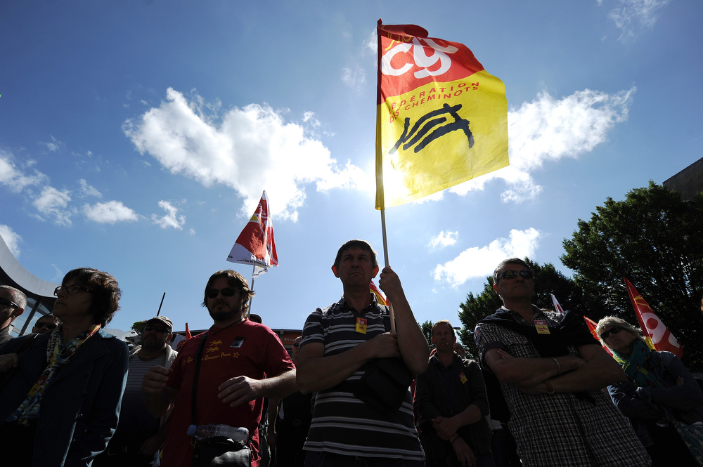 Description of . A man holds a CGT union flag as he takes part with other protestors in a demonstration called by workers of the French rail company SNCF on June 17, 2014 in front of Nantes train station, in Nantes, western France. France's longest rail strike in years rolled on for a second week on June 17 as lawmakers were set to debate a contentious debt-cutting reform plan opposed by unions. The crippling action, which comes as the tourist season enters a peak phase, has proved a key challenge for the embattled Socialist government, which has said it will not kowtow to the strikers. (JEAN-SEBASTIEN EVRARD/AFP/Getty Images)