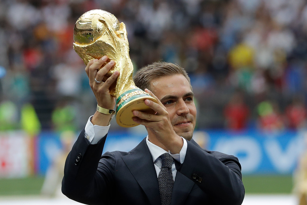 . Former German soccer team captain Philipp Lahm displays the trophy before the final match between France and Croatia at the 2018 soccer World Cup in the Luzhniki Stadium in Moscow, Russia, Sunday, July 15, 2018. (AP Photo/Matthias Schrader)