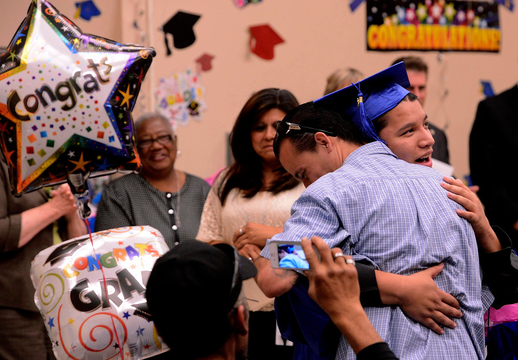 . Graduate Dominic Vasquez, right,  hugs his uncle Paul Gomez during Commencement Ceremonies at Carl And Dora Anderson School in San Bernardino May 21, 2013.  GABRIEL LUIS ACOSTA/STAFF PHOTOGRAPHER.
