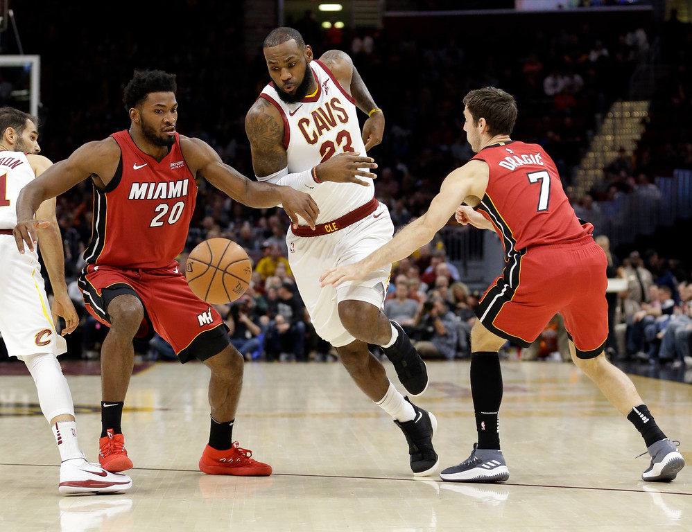 . Cleveland Cavaliers\' LeBron James (23) drives between Miami Heat\'s Justise Winslow (20) and Goran Dragic, from Slovenia, in the first half of an NBA basketball game, Tuesday, Nov. 28, 2017, in Cleveland. (AP Photo/Tony Dejak)