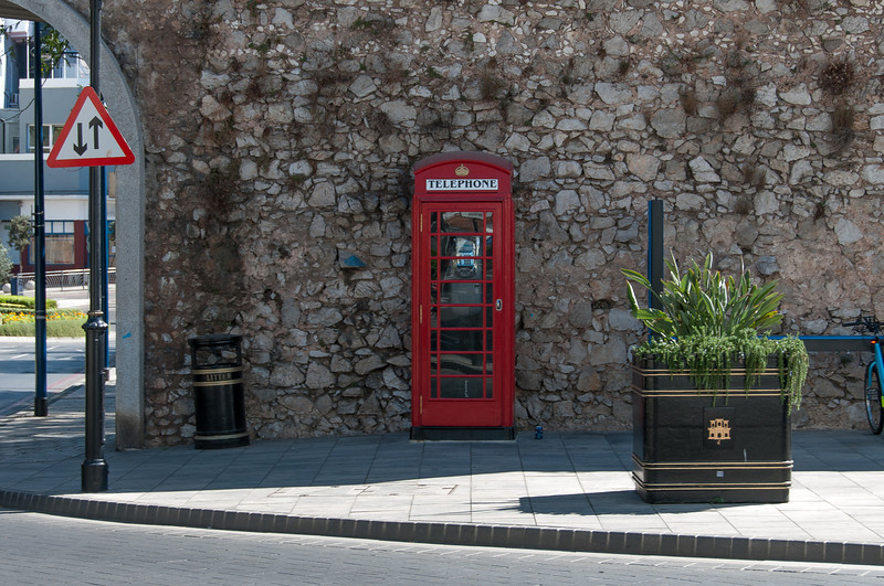 Red telephone booth at an empty street corner in Gibraltar