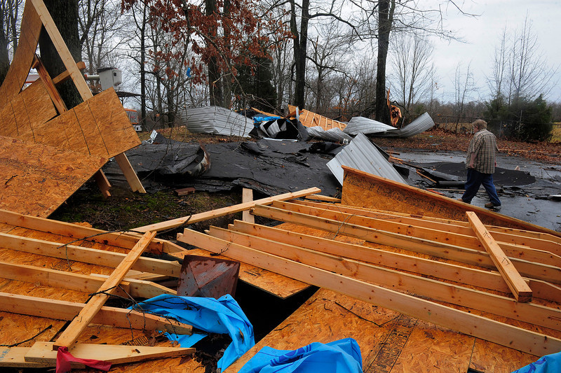 . Tom L. Ragsdale walks through rubble after a strong winds wrecked part of his home in Robertson County, Tenn., Wednesday Jan. 30, 2013.  Strong storms packing high winds blew through Tennessee early Wednesday, causing power outages and widespread damage.     (AP Photo/The Tennessean,John Partipilo)