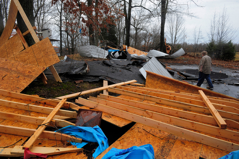 Description of . Tom L. Ragsdale walks through rubble after a strong winds wrecked part of his home in Robertson County, Tenn., Wednesday Jan. 30, 2013.  Strong storms packing high winds blew through Tennessee early Wednesday, causing power outages and widespread damage.     (AP Photo/The Tennessean,John Partipilo)