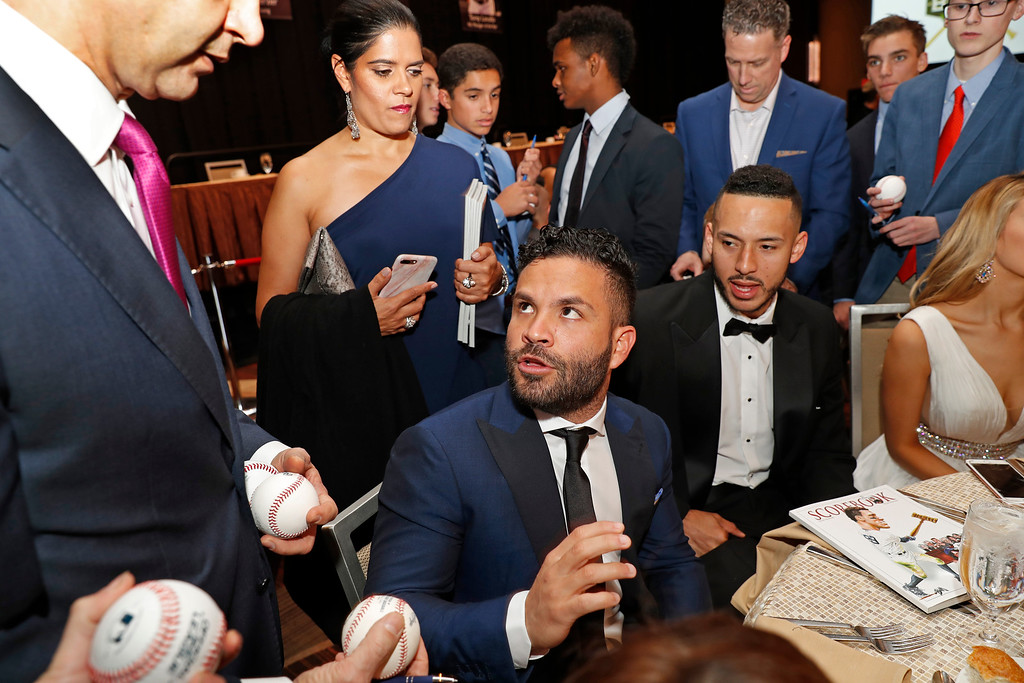 . American League Most Valuable Player Jose Altuve, center, of the Houston Astros speaks to fans as he sits beside teammate Carlos Correa, who received a community service award for his work during Hurricane Harvey, before the start of the New York Chapter of the Baseball Writers\' Association of America annual dinner in New York, Sunday, Jan. 28, 2018. (AP Photo/Kathy Willens)