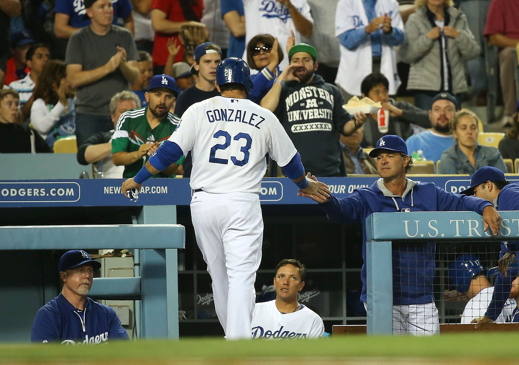 . Manager Dan Mattingly of the Los Angeles Dodgers congratulates Adrian Gonzalez #23 after Gonzalez scored in the third inning during the MLB game against the Colorado Rockies at Dodger Stadium on June 18, 2014 in Los Angeles, California.  (Photo by Victor Decolongon/Getty Images)