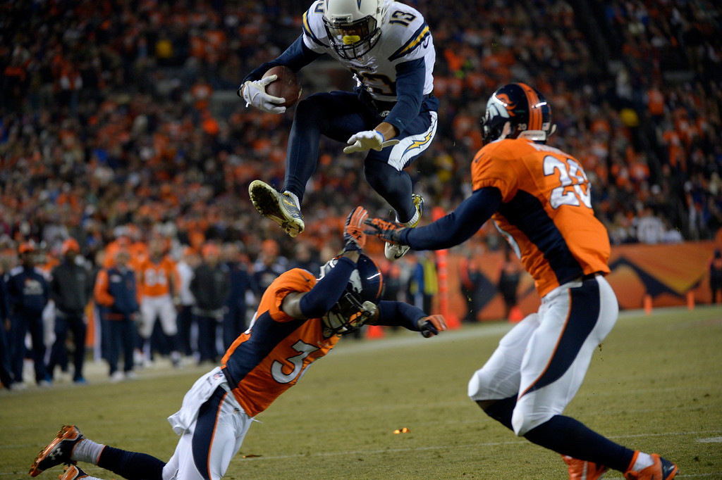 . DENVER, CO - DECEMBER 12: San Diego Chargers wide receiver Keenan Allen (13) takes to the air and over Denver Broncos cornerback Kayvon Webster (36) and into Denver Broncos strong safety Mike Adams (20) on his way to a touchdown during the second quarter. The Denver Broncos vs. the San Diego Chargers at Sports Authority Field at Mile High in Denver on December 12, 2013. (Photo by Joe Amon/The Denver Post)