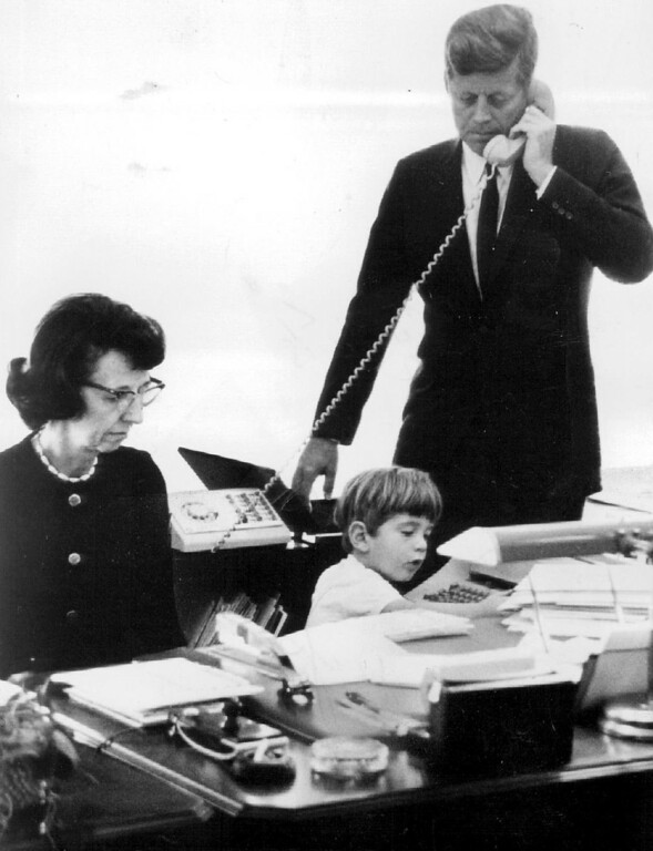 . Secretary Evelyn Lincoln works in the President\'s office with Kennedy as John Jr. busies himself in 1963. Denver Post file