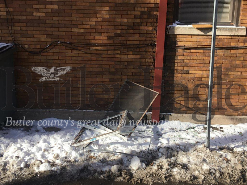 3 COLUMN PHOTO. A broken window and metal window frame lay on the ground in back of the Catholic Charities building in Butler, where police say a teenager Monday vandalized a room at the facility where he had been staying. Police arrested the suspect who is in the Butler County Prison.