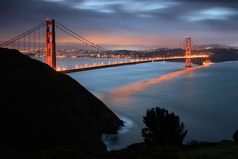 Spanning a deep, powerful tidal vent, the Golden Gate Bridge was completed in 1937, costing $35 million. With a span of 4,200 feet (1.2 km), it is 211 meters above the water. While approximately 100,000 vehicles cross the bridge every day, and thousands of tons of shipping pass beneath, nearly a quarter of the entire bay's water will flow beneath it in each daily tidal cycle. This tidal flow is forms an integral element in the bay's ecology.