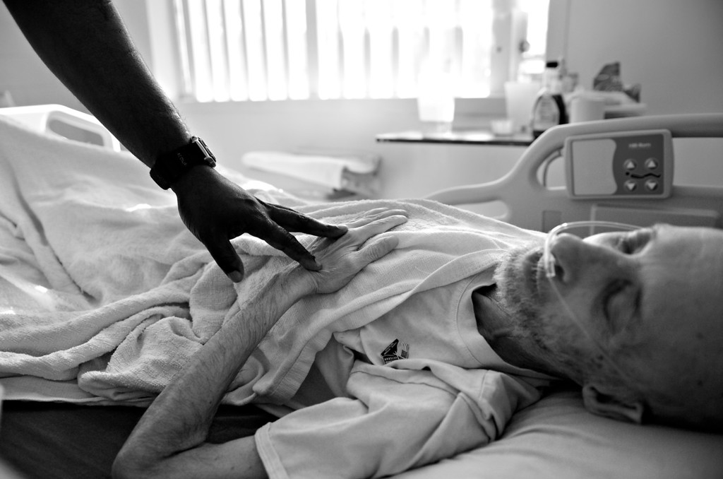 """. CANYON CITY, CO. - NOVEMBER 08: Wayne Rose, left, reaches out and touches Robert Bryan before leaving his room, November 08, 2012. \""""Cancer finally caught up to me,\"""" said Bryan. \""""I feel good about dying. I have done lots of bad things in my life and there is nothing in this world for me anymore.\"""" (Photo By RJ Sangosti/The Denver Post)"""