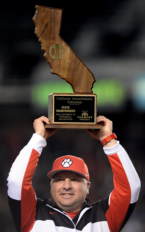 . Redlands East Valley High School head football coach Kurt Bruich raises the CIF State trophy after REV defeated Clayton Valley Charter 34-33 during the CIF-State Division II championship against Clayton Valley Charter on Saturday, December 20, 2014 at StubHub Center in Carson, Ca. (Photo by Micah Escamilla/Redlands Daily Facts)
